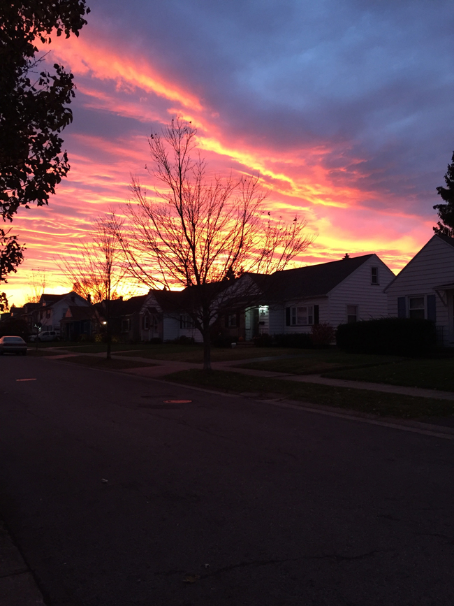 red-orange-yellow sunrise over house roofs
